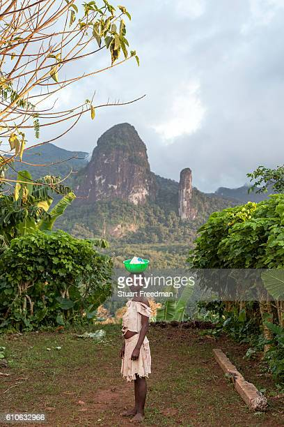 A child carrying a bowl on her head stands in from of the Pico de Príncipe and the Pico Cão Grande the two highest mountains on the island Principe...