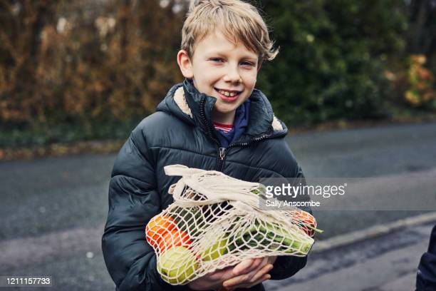child carrying food shopping - sally anscombe stock pictures, royalty-free photos & images
