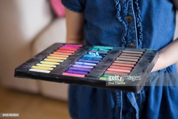 Child carrying pallette of multicoloured hair chalks