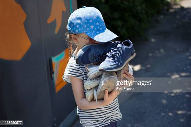 Child (6-7) carrying pile of old shoes for recycling at a recycling centre