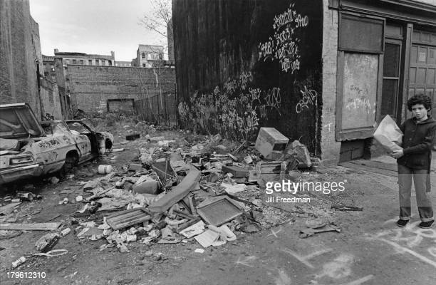 A child carrying shopping walks past rubbish and an abandoned car in Alphabet City New York City 1979
