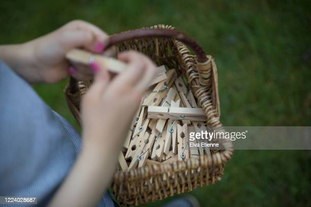 child carrying wicker basket full of wooden clothes pegs - clothespin stock pictures, royalty-free photos & images