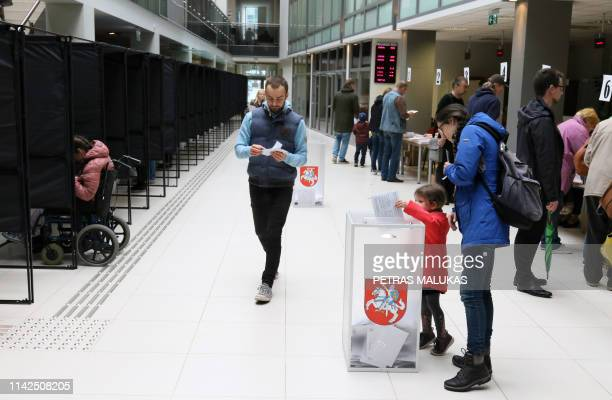 A child casts a ballot during an early vote two days ahead of the presidential elections at a polling station in Vilnius Lithuania on May 10 2019 For...