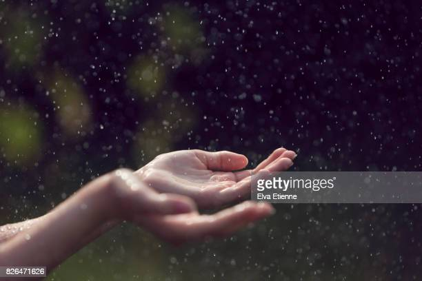 child catching falling raindrops in hands - rain stock-fotos und bilder