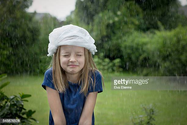Child caught in rain, using plastic bag as rain hat