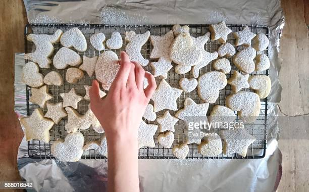 child choosing a cookie from a wire tray filled with freshly baked homemade cookies - icing sugar stock pictures, royalty-free photos & images