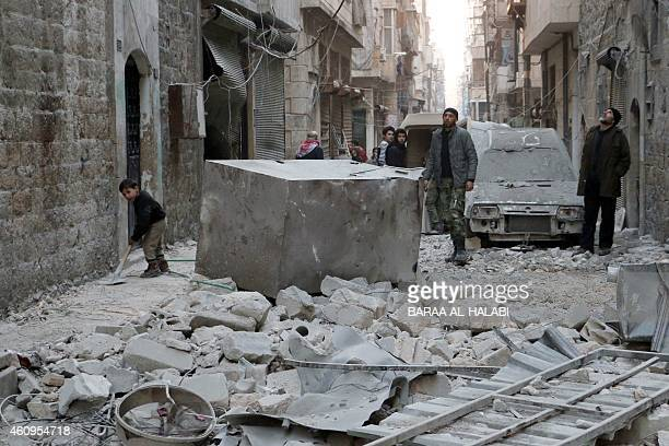 A child clears a pavement as people stand in a devastated street on January 1 2015 in the alKalasa neighbourhood of the northern Syrian city of...