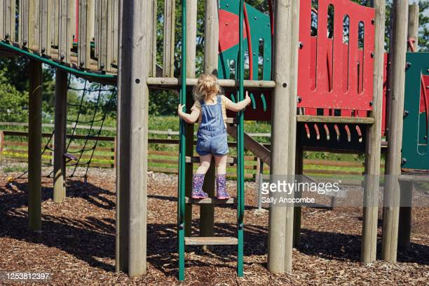 child climbing a ladder in a playground - britain playgrounds stock pictures, royalty-free photos & images