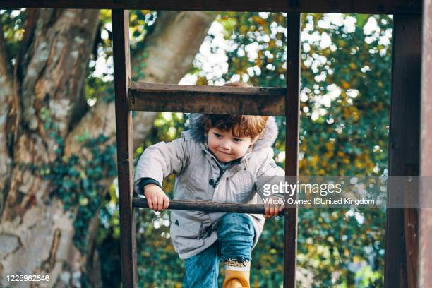 a child climbing a ladder with trees in the background. - climbing stock pictures, royalty-free photos & images