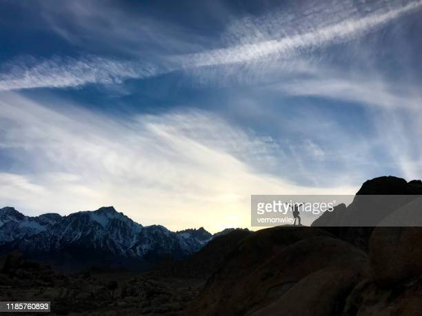 child climbing above the skyline of a beautiful mountain landscape. - mental wellbeing stock pictures, royalty-free photos & images