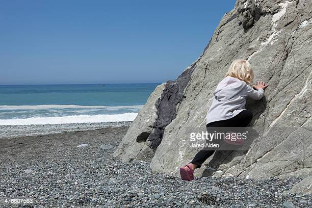 Child Climbing Boulder On Beach