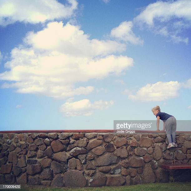Child climbing onto large rock wall