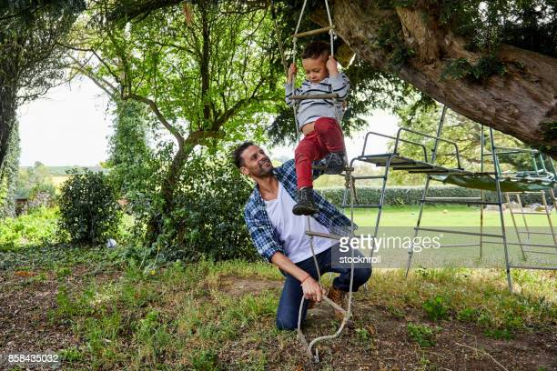 Child climbing rope ladder with father