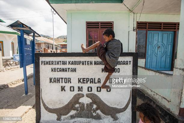 Child climbs the welcome sign to the village of Kampung Komodo. Komodo Island , August 3rd 2019