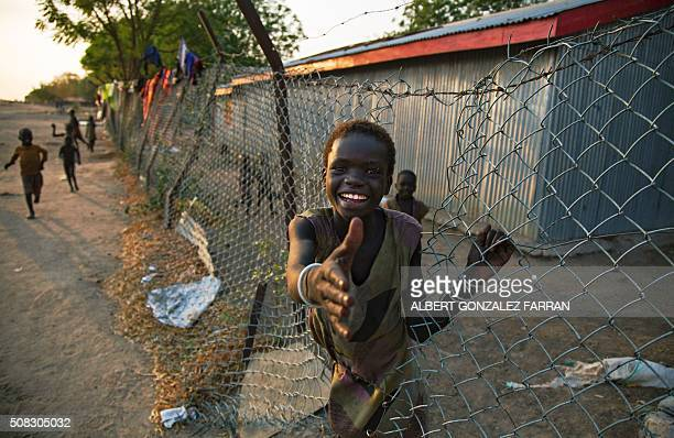 TOPSHOT A child climbs through a fence inside the former compound of the International Committee of the Red Cross in the halfemptied village of Leer...