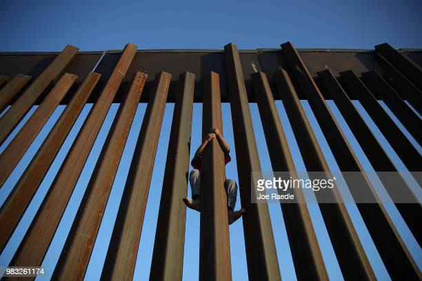 A child climbs up the Mexican side of the US/Mexico border fence on June 24 2018 in Sunland Park New Mexico The Trump administration's 'zero...