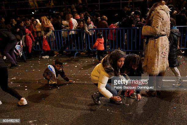 A child collect sweets from the ground after the 'Cabalgata de Reyes' or the Three Kings parade passed by on January 5 2016 in Madrid Spain The...