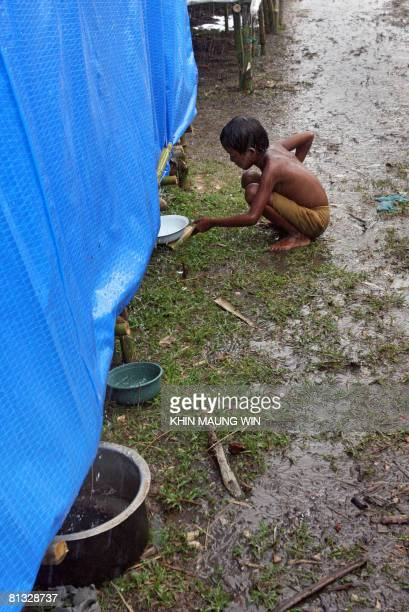 A child collects rain water running off of a tent at a camp for people displaced from Cyclone Nargis near the Irrawaddy Delta town of Labutta some...