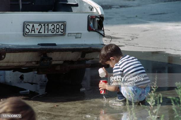 Child collects water in a puddle protected by a car on Alipasino Polje Avenue, known as Sniper Alley, at Sarajevo on August 23, 1993.