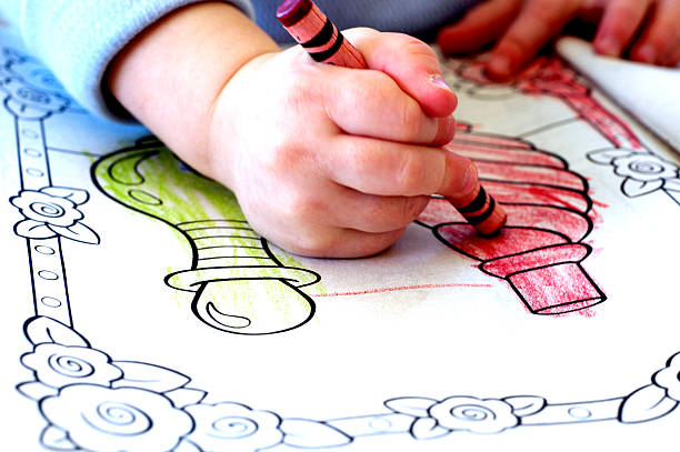 A Child Coloring In An Activity Book