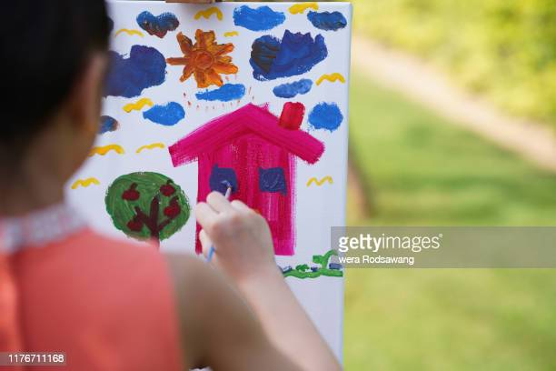 child concentrate with painting art selective focus on hand holding paintbrush - religious dress stock photos and pictures