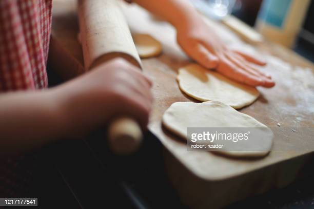 child cooking at home rolling out bread dough - fun stock pictures, royalty-free photos & images