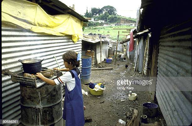 Child cooking on open fire outside shack