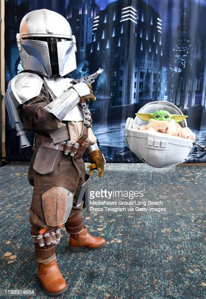 Child cosplaying as the Mandalorian poses for photos complete with his Baby Yoda companion during the Long Beach Comic Expo in Long Beach on...