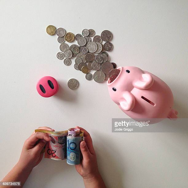 Child counting money in piggy bank