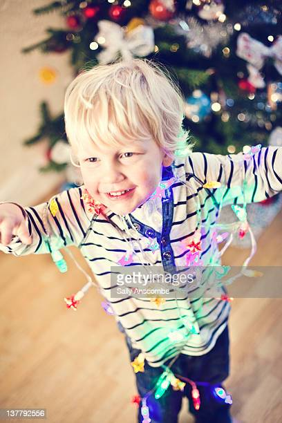 Child covered in multi coloured fairy lights