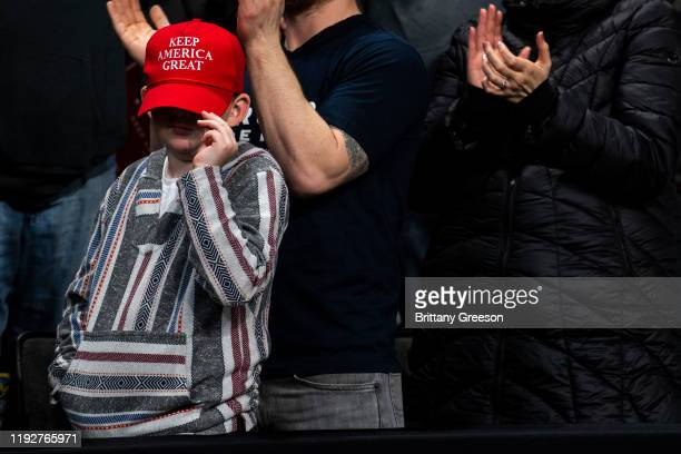 """Child covers his face with a hat as President Donald Trump speaks at a """"Keep America Great"""" campaign rally at the Huntington Center on January 9,..."""