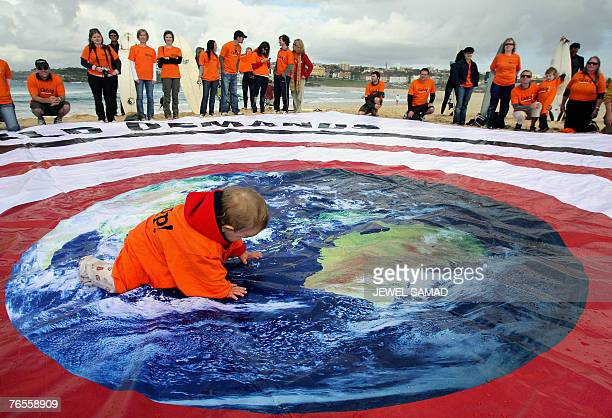 A child crawls across a huge banner as environmental activists demonstrate at Bondi beach in Sydney 07 September 2007 aiming to allure the attention...