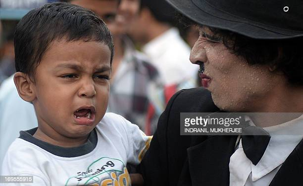 A child cries as he is held by Indian street performer Somnath Sohavane entertaining crowds with his enactment of Charlie Chaplin's 'The Tramp' at...