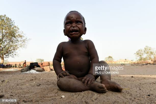 A child cries as he sits on the ground at the internally displaced people camp occupied largely by women and children affected by herders and...