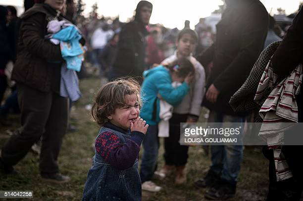 A child cries as people rush to receive distributed food in the makeshift camp at the GreekMacedonian border near the Greek village of Idomeni on...