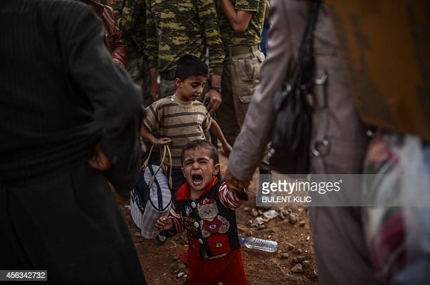 Child cries as Syrian Kurdish people arrive after crossing the border between Syria and Turkey after several mortars hit both side in the...