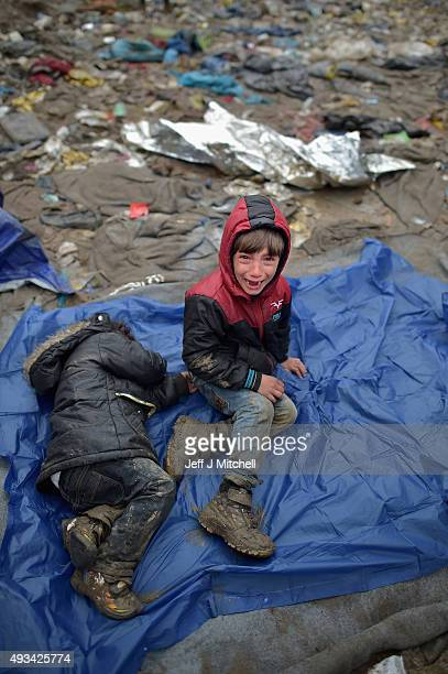 A child cries sitting in the mud as migrants wait in the field near the crossing border between Serbia and Croatia on October 20 2015 near the...