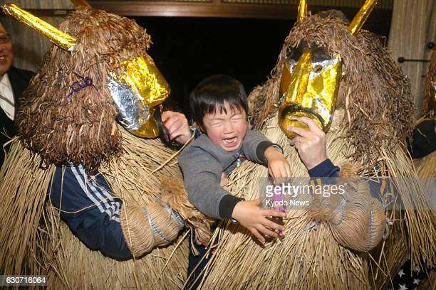 A child cries while being lifted by men disguised as 'Namahage' wearing a demonlike mask and a costume made of straw in Oga Akita Prefecture...