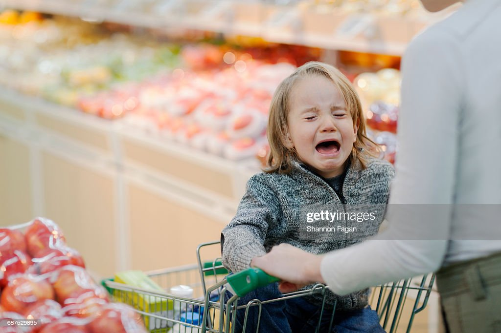 Child crying in shopping cart in supermarket : Stock Photo