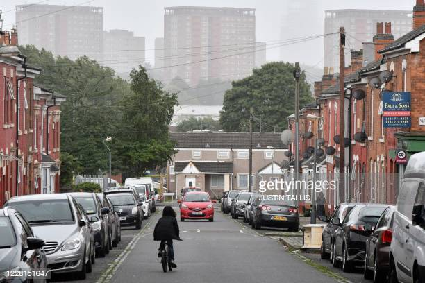 Child cycles down a residential street in the Lozells area of Birmingham, central England on August 22 as Britain's second-city, home to more than...