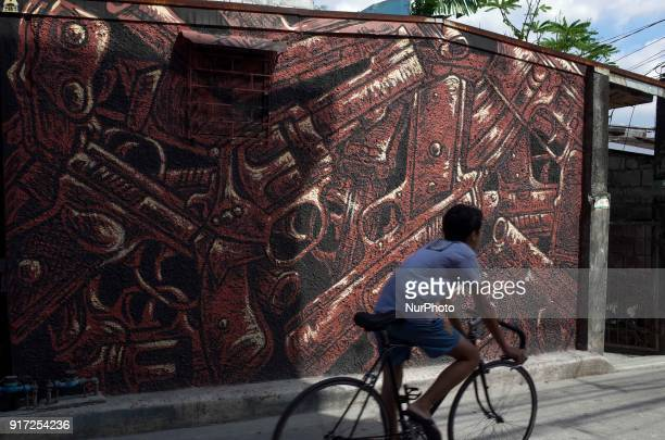 A child cycles past a mural depicting guns at a village in Manila Philippines on Monday February 12 2018 Philippine President Rodrigo Duterte...