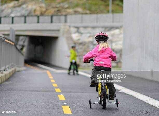 Child cycling on cycling lane in a small European city.