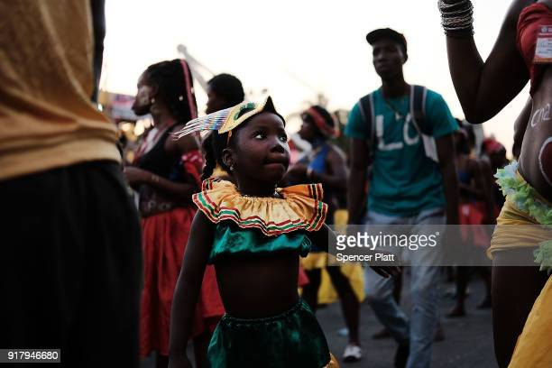 A child dances as performers march through the streets of PortauPrince during the last day of Carnival on February 13 2018 in PortauPrince Haiti...