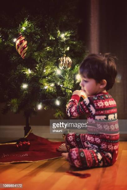 child decorates christmas tree - children only stock pictures, royalty-free photos & images