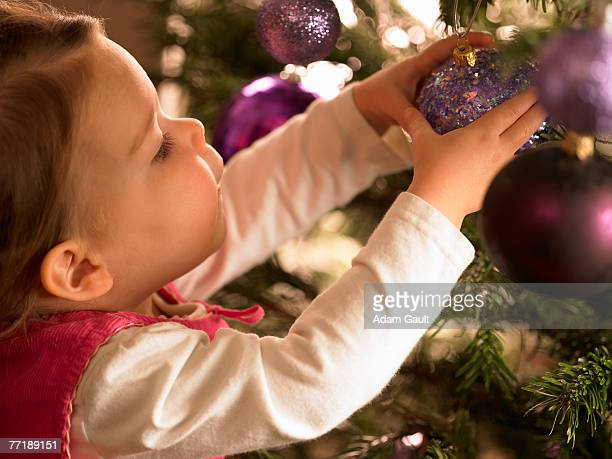 A child decorating a Christmas tree