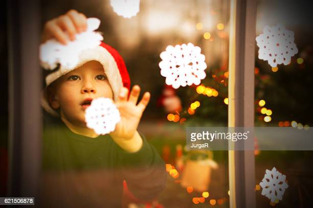 child decorating a window with snowflakes for christmas - ornato foto e immagini stock