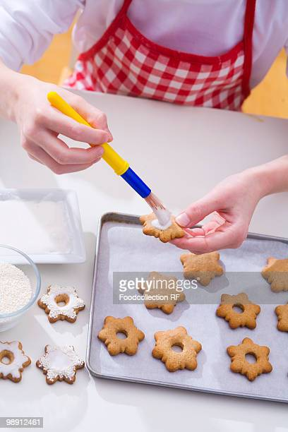 child decorating christmas biscuits, elevated view, close-up - basting brush stock photos and pictures