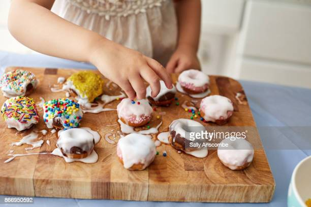 Child decorating doughnut with sprinkles