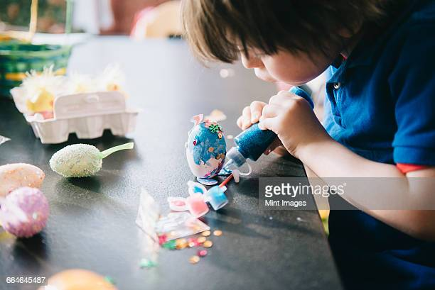 a child decorating eggs at easter with glitter, glue and paint.  - easter stock pictures, royalty-free photos & images