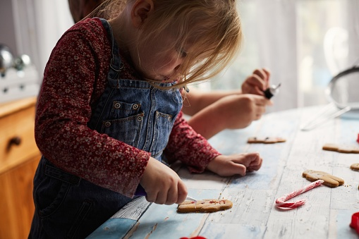Child decorating gingerbread biscuits - gettyimageskorea
